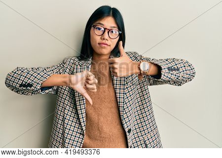 Young chinese woman wearing business style and glasses doing thumbs up and down, disagreement and agreement expression. crazy conflict