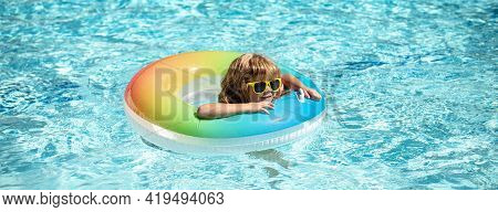 Summertime Vacation. Summer Kids Weekend. Funny Boy In Swiming Pool On Inflatable Rubber Circle At A