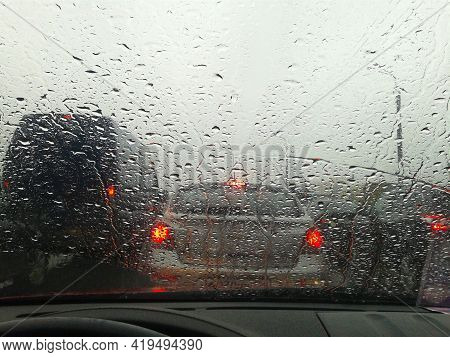 Street In The Heavy Rain. Water Drops Or Rain In Front Of Mirror Of Car On Road Or Street.