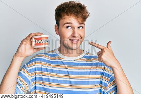 Young caucasian man holding denture smiling looking to the side and staring away thinking.