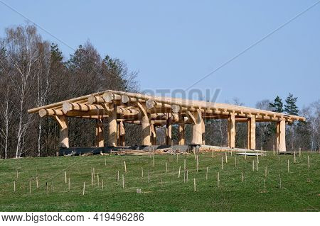 Wooden Gazebo, Standing Under The Blue Sky Near The Forest.
