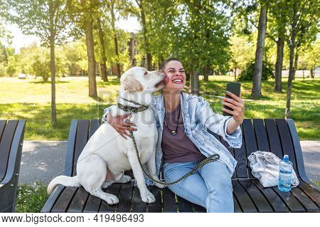 Young Beautiful Woman Sitting With Her Pet Dog A Golden Labrador Retriever On A Bench Wants To Take