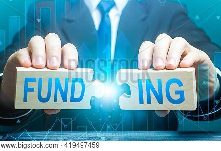 Businessman Connects Puzzles With The Word Funding. Investing In A Business Project, Raising Funds.