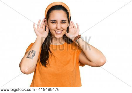 Young hispanic woman wearing casual clothes trying to hear both hands on ear gesture, curious for gossip. hearing problem, deaf
