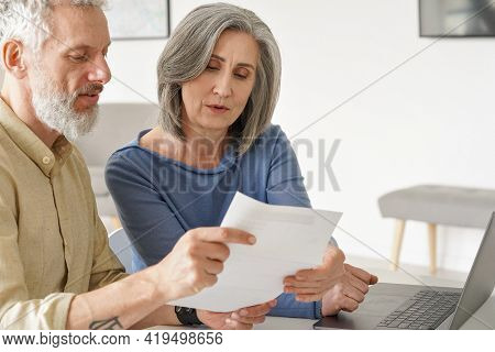 Older Mature Couple Checking Bank Documents Using Laptop At Home. Senior Mid Age Retired Man And Wom