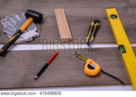 Equipment Or Tools To Install Laminate Floor. Rubber Hammer, Cutter, Protective Gloves, Pencil, Spir
