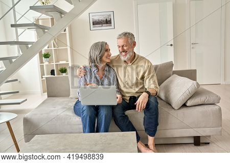 Happy Senior Mature Family Couple Using Laptop Computer At Home. Smiling Mid Aged 50s Husband Embrac