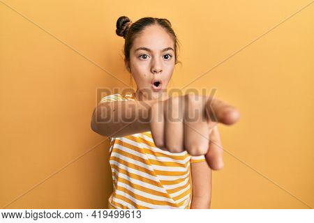 Beautiful brunette little girl wearing casual striped t shirt pointing with finger surprised ahead, open mouth amazed expression, something on the front