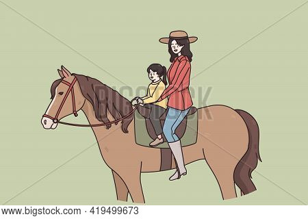 Summer Activities And Riding Concept. Young Smiling Woman Mother And Small Daughter Sitting On Horse