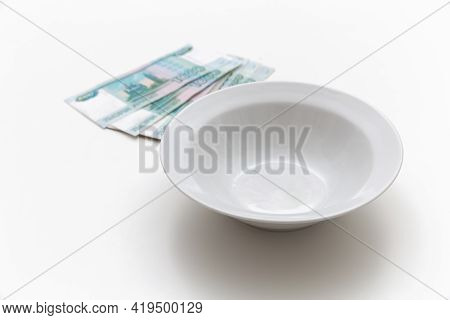 There Is Money, Rubles Near An Empty Plate, Money On A White Background. Hunger. No Money To Buy Foo