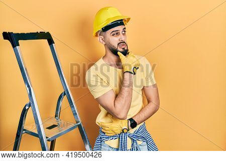 Handsome man with beard by construction stairs wearing hardhat thinking worried about a question, concerned and nervous with hand on chin
