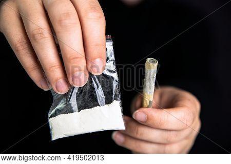 Drug Dealer Giving Drugs In A Plastic Bag, Cocaine,heroin,speed Or Other Drugs On Dark Black Backgro