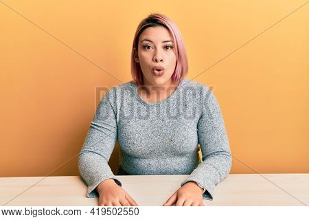 Hispanic woman with pink hair wearing casual clothes sitting on the table scared and amazed with open mouth for surprise, disbelief face