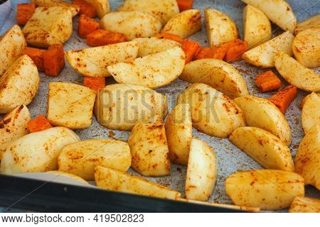 Potatoes And Carrots With Spices On A Baking Tray Ready To Be Baked. Close Up.