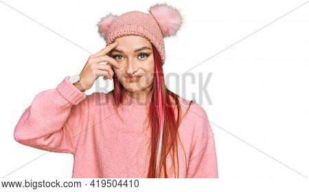Young caucasian woman wearing casual clothes and wool cap worried and stressed about a problem with hand on forehead, nervous and anxious for crisis