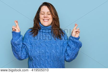 Young plus size woman wearing casual clothes gesturing finger crossed smiling with hope and eyes closed. luck and superstitious concept.