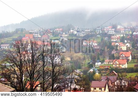 Horizontal Shot Of A Shaped Winter Houses Against Leafless Trees And Small Houses On Mountains Durin