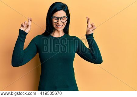 Young caucasian woman wearing casual clothes and glasses gesturing finger crossed smiling with hope and eyes closed. luck and superstitious concept.