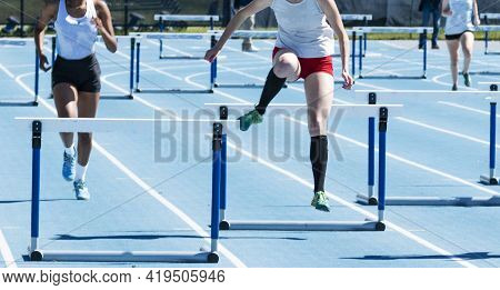 High School Girls Competing In The 400 Meter Hurdles On A Blue Track At A Track And Field Race.