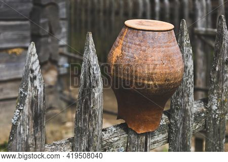 Traditional Slavic Decor In Village. Clay Vintage Terra Cotta Water Pot On Wooden Fence At Countrysi