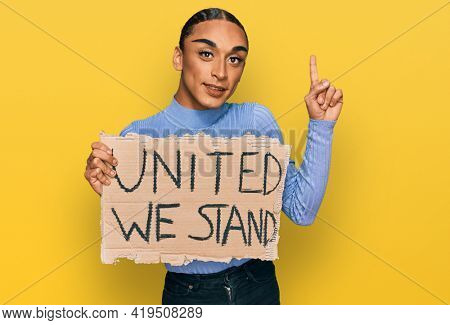 Hispanic transgender man wearing make up and long hair holding united we stand banner surprised with an idea or question pointing finger with happy face, number one
