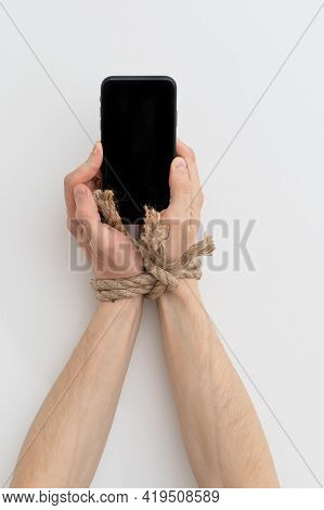 Internet Addiction Or Social Media Addiction. Hands Tied With A Rope Hold A Smartphone