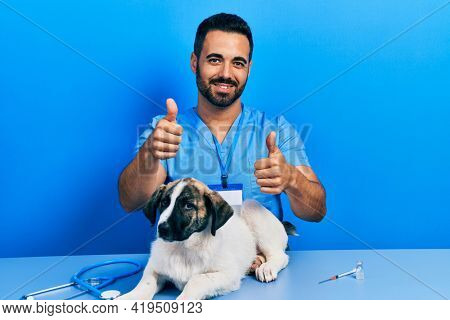 Handsome hispanic veterinary man with beard checking dog health pointing fingers to camera with happy and funny face. good energy and vibes.