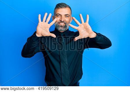 Middle age handsome man wearing business shirt and tie showing and pointing up with fingers number ten while smiling confident and happy.