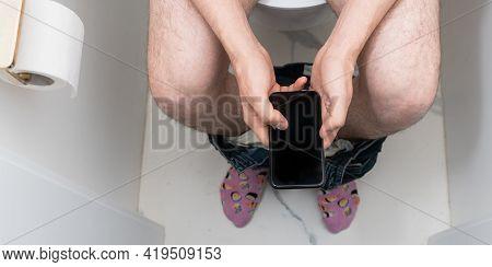 Man Using Mobile Phone In Toilet. Internet Addiction Or Social Media Addiction