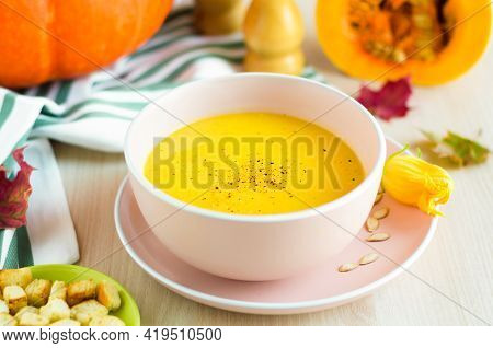 Foliage Leaves, Flowers And Creamy Pumpkin Soup With Vegetables, Seeds And Croutons In A Bowl, Close