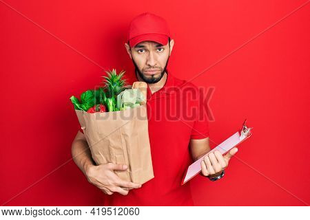 Hispanic man with beard wearing courier uniform with groceries from supermarket and clipboard depressed and worry for distress, crying angry and afraid. sad expression.