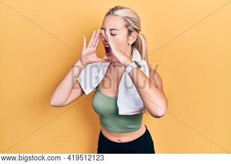 Young blonde girl wearing sportswear and towel shouting angry out loud with hands over mouth
