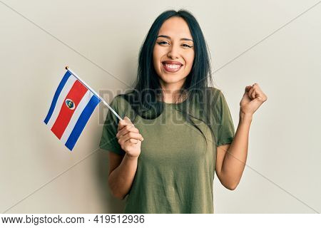 Young hispanic girl holding costa rica flag screaming proud, celebrating victory and success very excited with raised arm