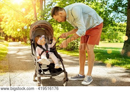 family, fatherhood and people concept - father with child sitting in stroller fastening seatbelt at summer park