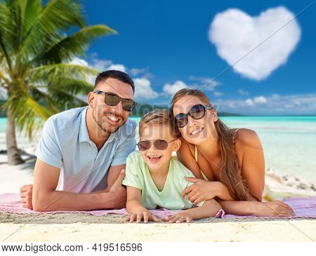 family, travel and tourism concept - happy mother, father and little son in sunglasses lying on blanket over tropical beach in french polynesia and heart shaped cloud on background