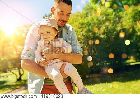 family, fatherhood and people concept - happy smiling father with baby daughter at summer park