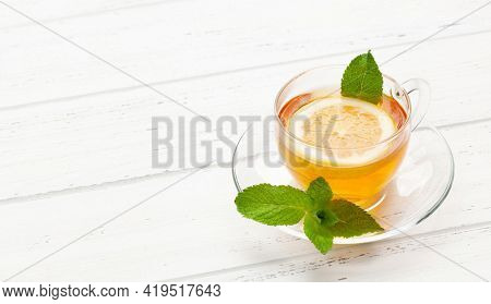 Herbal tea with mint and lemon. Tea cup on wooden table. With copy space
