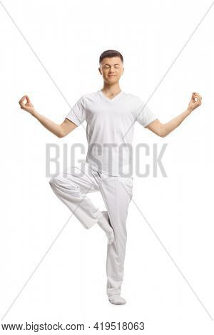 Full length portrait of a young man in white clothes standing in a yoga pose with one lifted leg isolated on white background