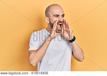 Young bald man wearing casual white t shirt shouting angry out loud with hands over mouth