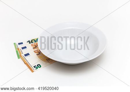 There Is Money Under An Empty Plate, Euros On A White Background. Hunger. No Money To Buy Food. Ther