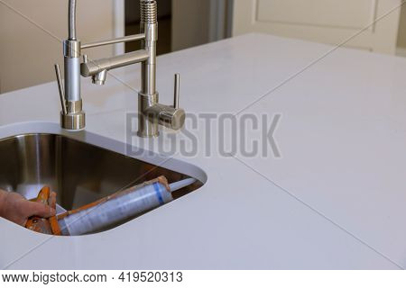 Worker Installing Granite Sink In Transparent Silicone Sealant Is Applied To The Edge Of The Kitchen