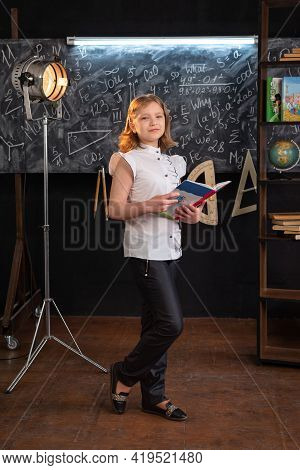 A Girl In Strict Clothes Stands At A School Blackboard With Inscriptions