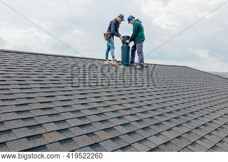 Construction Workers Installing Chimney And Building Construction Concept. Contractor Builder With B