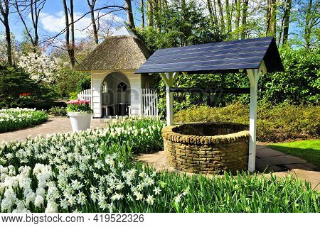 Small Cottage And Wishing Well Surrounded By Spring Daffodil Flowers At Keukenhof Gardens, Netherlan