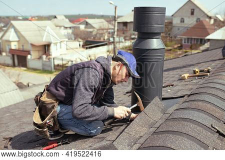 A Professional Master Roofer With Hammer Repairs The Roof. Repair Asphalt Shingles Or Bitumen Tiles