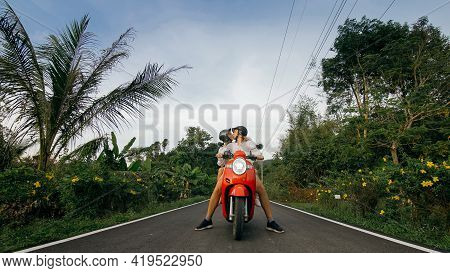 Love Couple On Red Motorbike In White Clothes To Go On Forest Road Trail Trip. Two Caucasian Tourist