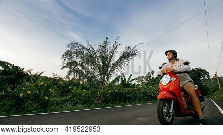 Man On Red Motorbike In White Clothes Drive On Forest Road Trail Trip. One Men Caucasian Tourist Go