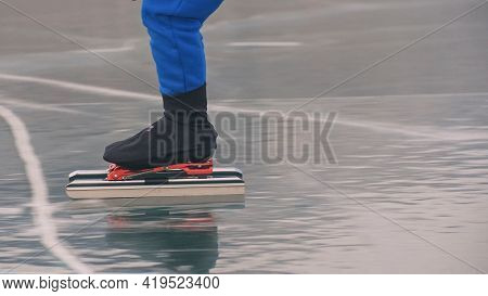 The Child Train On Ice Speed Skating. The Legs In Skates Close Up. The Kid Girl Skates In The Winter