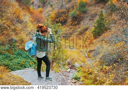Female Tourist With A Backpack Admires The Mountain Scenery. A Red-haired Woman Ties Her Hair On The