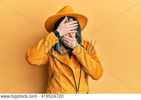 Young modern girl wearing yellow hat and leather jacket covering eyes and mouth with hands, surprised and shocked. hiding emotion